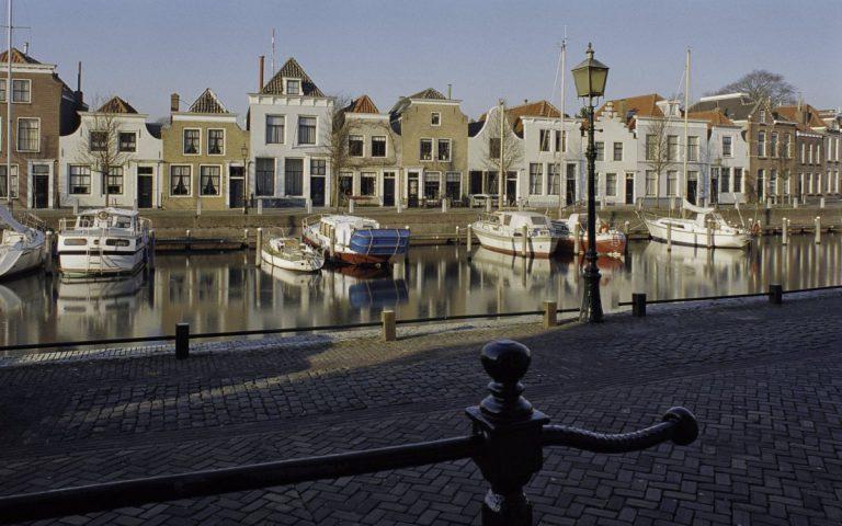 Afbeelding van een kanaal met boten en huizen op de achtergrond